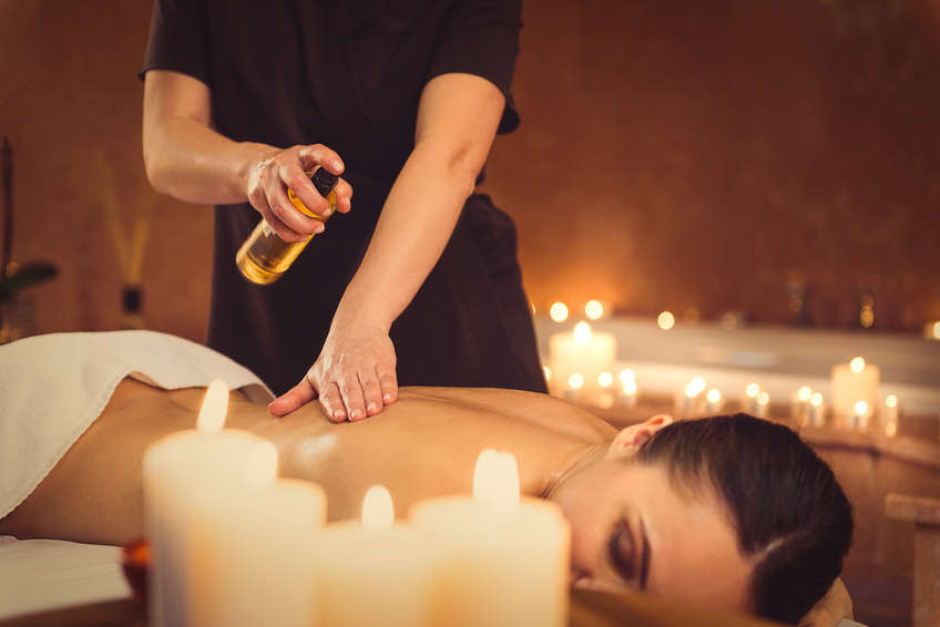 Ready for massage. Calm young woman is lying on massage table with relaxation. Masseuse is standing and pouring oil on her body